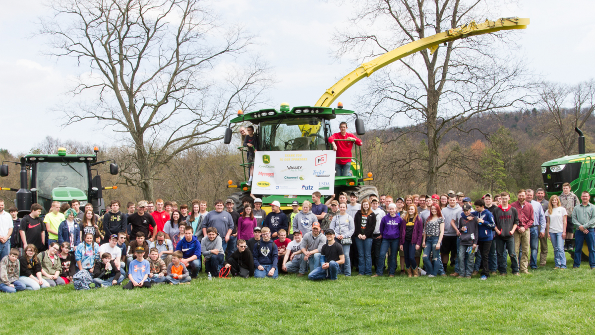 People standing in front of three tractors