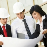 Two men and a woman looking at plans